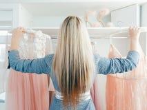 Fashion boutique personal assistant evening gowns. Fashion boutique. Back view of female personal assistant holding luxury evening gowns stock image