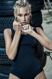 Fashion boxer woman in a black sportswear and with blue boxing gloves. Royalty Free Stock Photos