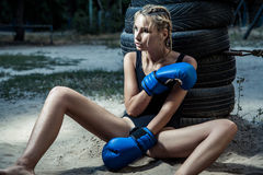 Fashion boxer woman in a black sportswear and with blue boxing gloves. Outdoor workout of young blonde woman Stock Image