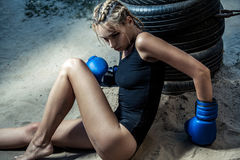 Fashion boxer woman in a black sportswear and with blue boxing gloves. Outdoor workout of young blonde woman royalty free stock photo