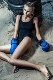 Fashion boxer woman in a black sportswear and with blue boxing gloves. Outdoor workout of young blonde woman Royalty Free Stock Image