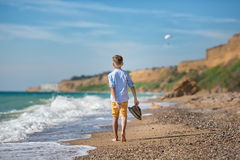 Fashion boy on the beach with hat and sun glasses Stock Photos