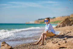 Fashion boy on the beach. With hat and sun glasses Royalty Free Stock Photography