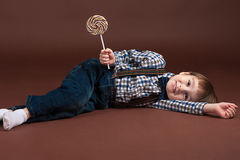 Fashion boy lying on the floor with a lollipop Royalty Free Stock Photography