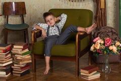 Fashion boy sits on a chair Royalty Free Stock Photo