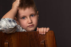 Fashion boy sits on a chair Stock Images