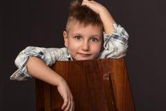 Fashion boy sits on a chair Stock Photos