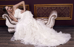 Fashion bride with blond hair in luxurious dress posing in interior. Fashion interior photo of glamour bride with blond hair in luxurious elegant dress lying on stock photography