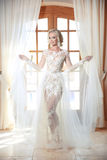 Fashion bride model in wedding dress posing in front of curtains Royalty Free Stock Photo