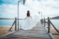 Fashion bride walking down pier on the beach in a white dress. Beautiful girl walks barefoot down the beach. royalty free stock photos