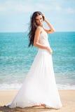 Fashion bride walking down the sea coast in a white dress. Beautiful girl walks barefoot down the beach. Royalty Free Stock Image