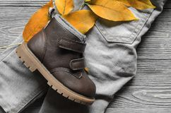 Fashion brown leather kids shoe and denim pants and accessories. Autumn concept Royalty Free Stock Photo