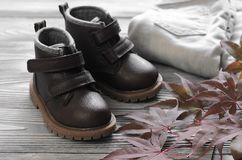 Fashion brown leather kids shoes, denim pants and accessories. a Royalty Free Stock Photo