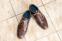 Fashion brown men`s shoes on a light brown ceramic tiles Stock Image