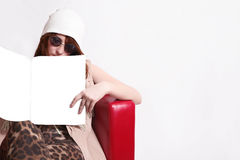 Fashion brunette girl in a cap and trendy round sunglasses is re Stock Photos
