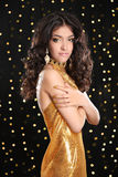 Fashion brunette girl in golden dress with Long curly hair, beau Royalty Free Stock Images