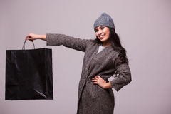 Fashion brunette girl hold shopping bag in hand. Fashion brunette girl portrait isolated on grey background. Happy girl hold shopping bag wear in coat and hat Royalty Free Stock Photos