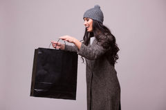 Fashion brunette girl look in shopping bag. Fashion brunette girl portrait isolated on grey background. Happy girl hold shopping bag wear in coat and hat. Sales Stock Image