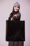 Fashion brunette girl pointed shopping bag. Fashion brunette girl portrait isolated on grey background. Happy girl hold shopping bag wear in coat and hat. Sales Royalty Free Stock Photos