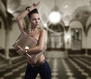 Fashion brunette in jeans with big bag and hand near the head Royalty Free Stock Images