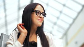 Fashion brunette model with bags looking at camera and smiling after shopping in the modern light mall.  stock footage