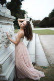 Fashion brunette model posing in rose long chiffon dress. By sculpture Royalty Free Stock Photo