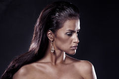 Fashion brunette. Portrait of beautiful woman wearing earrings. Portrait of beautiful sad woman wearing earrings. Over black background Stock Photo