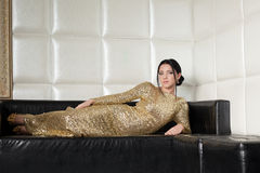 Fashion brunette woman in gold dress on sofa Royalty Free Stock Photos