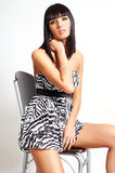 Fashion brunette woman looking down. Elegant brunette woman wearing a zebra dress and sitting on a chair Stock Photos