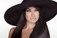 Fashion brunette woman model posing in black hat isolated on whi Royalty Free Stock Photo