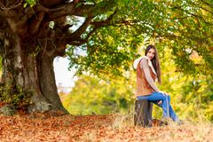 Fashion brunette woman with suitcase at autumn Stock Photo