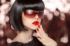 Fashion brunette woman in sunglasses. Black bob hairstyle. Red l Royalty Free Stock Images
