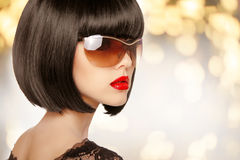 Fashion brunette woman in sunglasses. Black bob hairstyle. Red l Royalty Free Stock Image