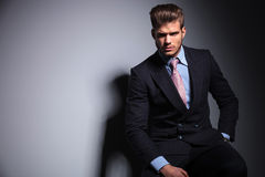 Fashion business man in suit and tie is sitting stock photography