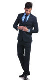 Fashion business man un buttoning his suit and looking down stock photography