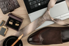 Fashion and business, notebook, shoes, cufflinks, cigar and tie on a wooden table as background. View from above Royalty Free Stock Images
