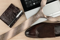 Fashion and business, notebook, shoes and tie on a wooden table as background. Top view Stock Image