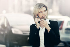 Fashion business woman calling on cell phone next to her car Royalty Free Stock Photos