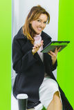 Fashion business woman dressed in coat holding tablet sitting on window sill Royalty Free Stock Photo