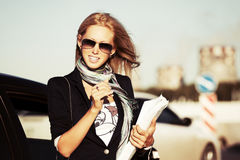 Fashion businesswoman with financial papers by car Royalty Free Stock Image