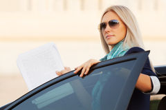 Fashion business woman with financial papers by her car Royalty Free Stock Photography