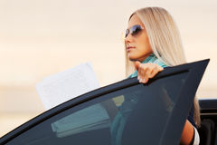 Fashion business woman with financial papers by her car Royalty Free Stock Image