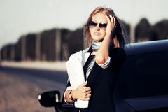 Fashion business woman with financial papers by her car Royalty Free Stock Photo