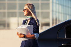 Fashion business woman with financial papers next to car Stock Photos