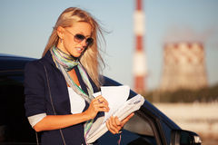 Fashion business woman with financial papers next to her car Stock Images