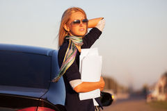 Fashion business woman with financial papers next to her car Royalty Free Stock Image