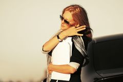 Fashion business woman with financial papers next to her car royalty free stock photography
