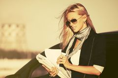 Fashion business woman with financial papers next to her car stock image