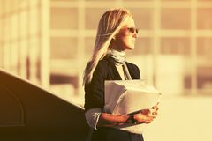 Fashion business woman with financial papers next to her car stock photos