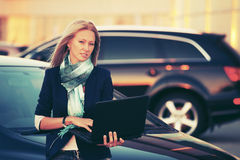 Fashion business woman with laptop standing next to her car Stock Image